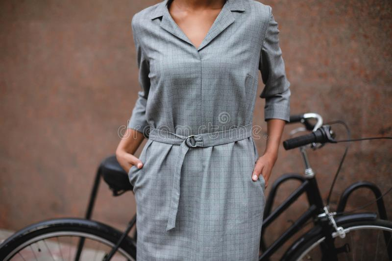 Close up photo of woman body in gray dress standing and holding hands in pockets. Young lady standing on street with. Bicycle on the background royalty free stock photo