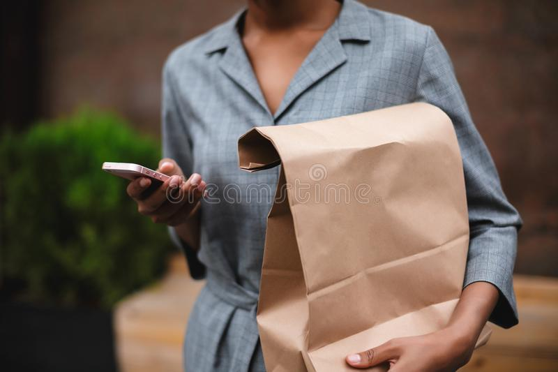Close up photo of woman body in gray dress standing and holding paper bag. Photo of woman hands with cellphone and paper. Bag on the street royalty free stock photography