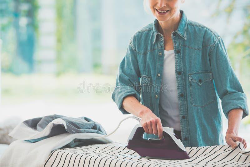 Close-up photo of woman ironing stock photo