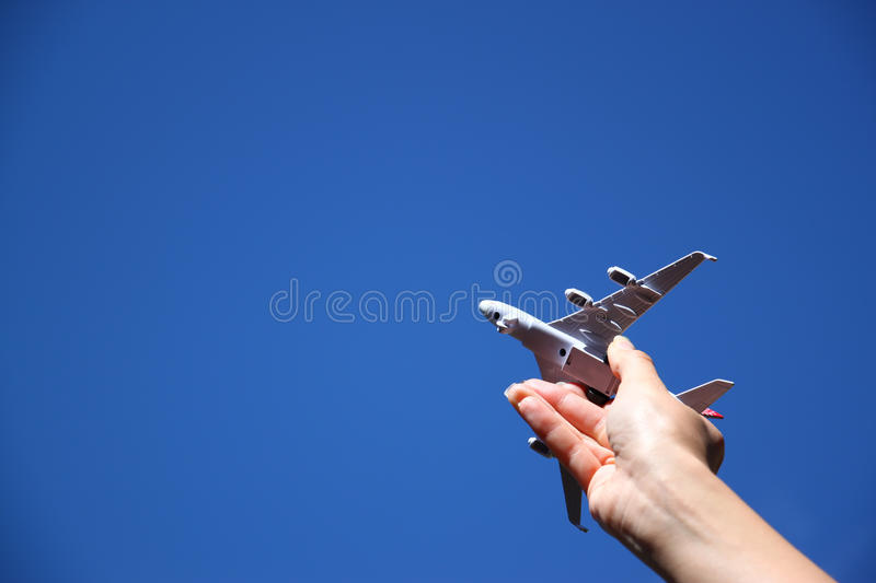 Close up photo of woman's hand holding toy airplane against blue sky with clouds royalty free stock photo