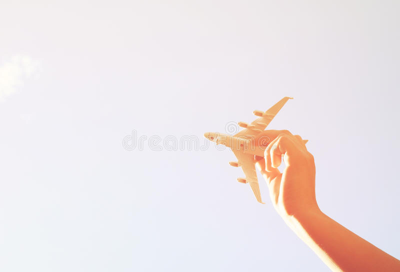 Close up photo of woman's hand holding toy airplane against blue sky with clouds royalty free stock photos