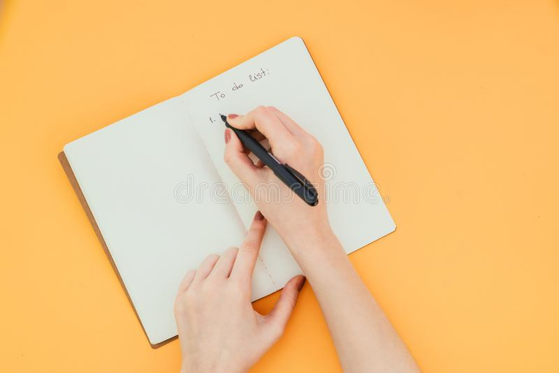 Close-up photo of a woman`s hand writing a to-do list in a clean notebook on an orange background. A view from above. Copyspace Flatlay royalty free stock image