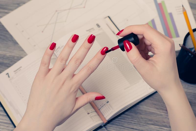 Close up photo of woman`s hands painting fingernails at workplac. E royalty free stock images