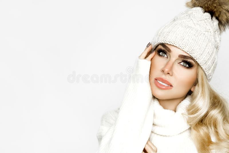 Close up photo of a young beautiful happy winter fashion girl on a white background. The model is wearing a stylish white knitted. Winter beanie and sweater royalty free stock photo