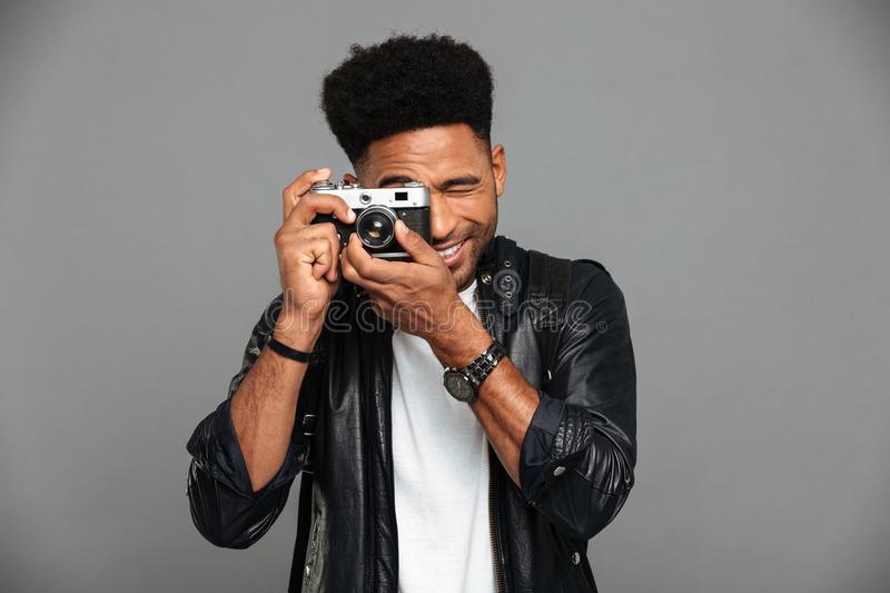 Close-up photo of young cheerful african man looking through retro cameras objective while taking photo royalty free stock photos