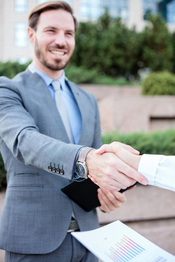 Close up photo of young female and male business people shaking hands after a successful meeting in front of an office building. S royalty free stock photo