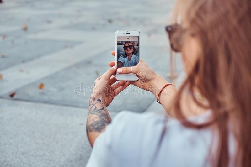 Close-up photo of young girl in sunglasses makes a selfie outdoors. Close-up photo of a young girl in sunglasses makes a selfie outdoors royalty free stock photography