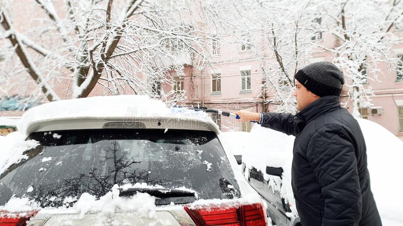 Close up photo of young handsome man in black coat and hat trying to clean up snow covered white car after blizzard with stock photo