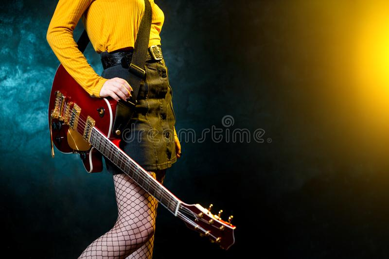 Close-up photo of young hipster woman legs and red guitar in neon lights. Rock musician is playing electrical guitar. 90s style concept stock image