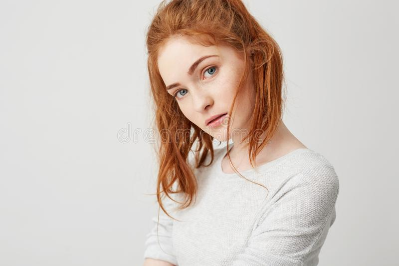 Close up of young tender girl with beautiful red foxy hair looking at camera over white background. Copy space. stock image