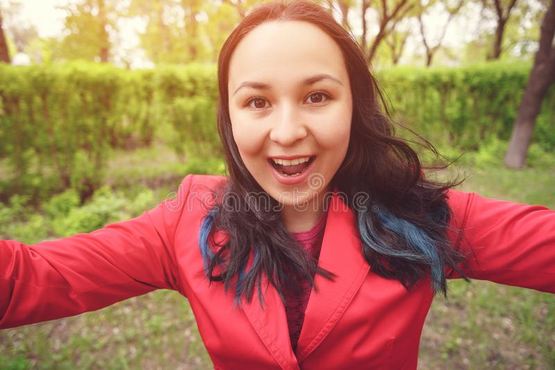Close-up photo. A young woman in red clothes on the street takes a selfie, looks at the camera and smiles royalty free stock photo