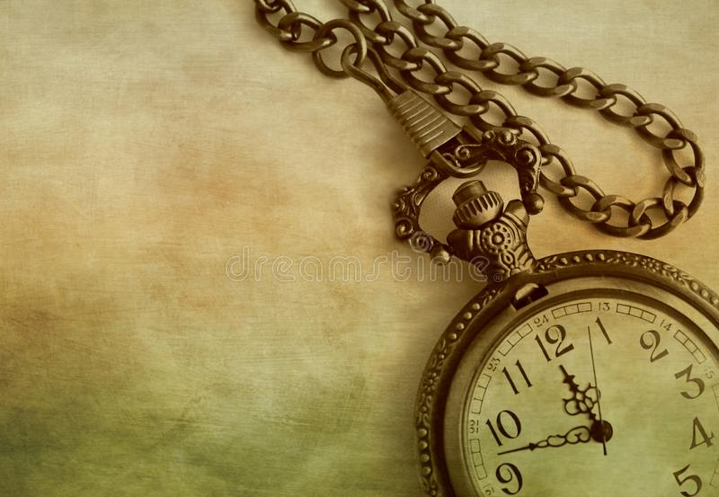 Artistic close-up of antique pocket watch and chain on colorful textured background with copy space royalty free stock photo