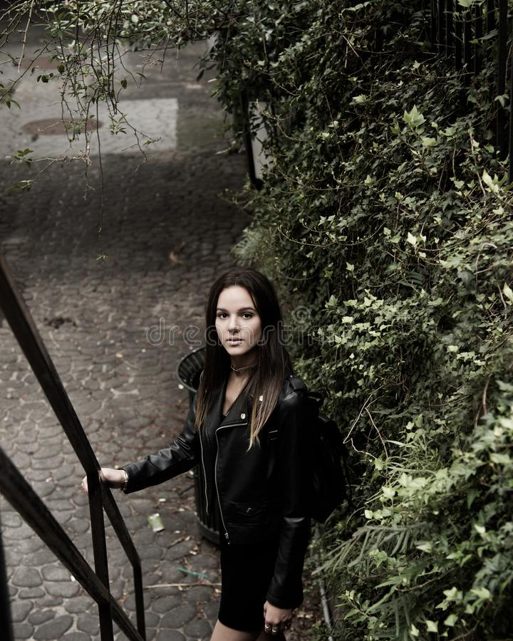 Close Up Photograph of Woman With Black Leather Jacket Standing Beside Stair Handle stock image
