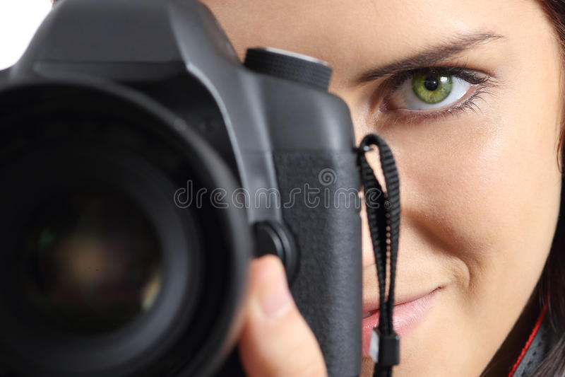 Close up of a photographer photographing with a dslr camera. Close up of front view of a photographer woman eye photographing with a dslr camera royalty free stock image