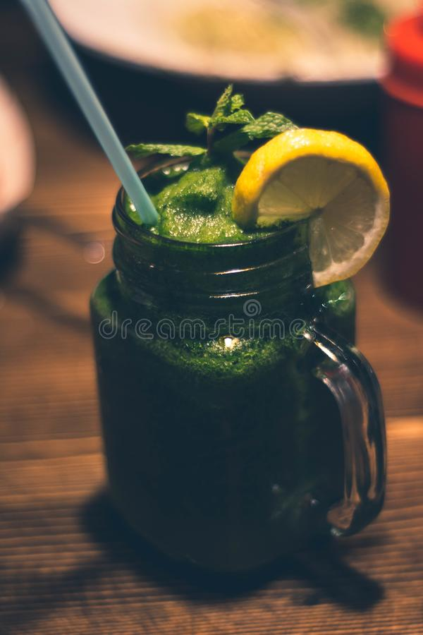 Close-up Photography of Clear Glass Mason Jar Mug With Green Juice and Sliced Citrus Toppings royalty free stock photo
