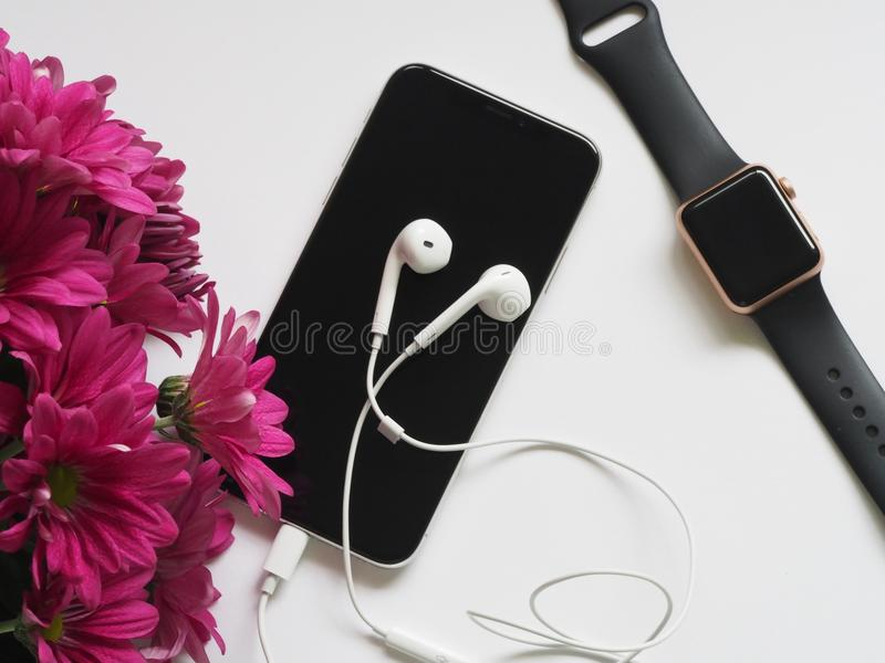 Close-Up Photography of Earphones on Top of Iphone 6 Near Flowers stock photography