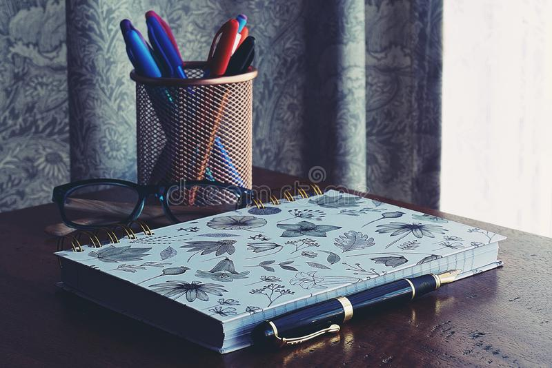 Close-Up Photography of Notebook Near Pens royalty free stock photos