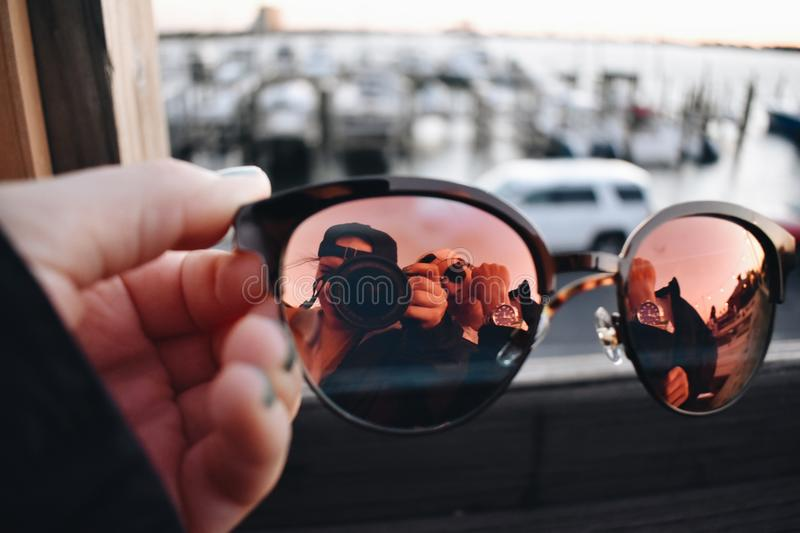 Close-Up Photography of a Person Holding Sunglasses stock photos