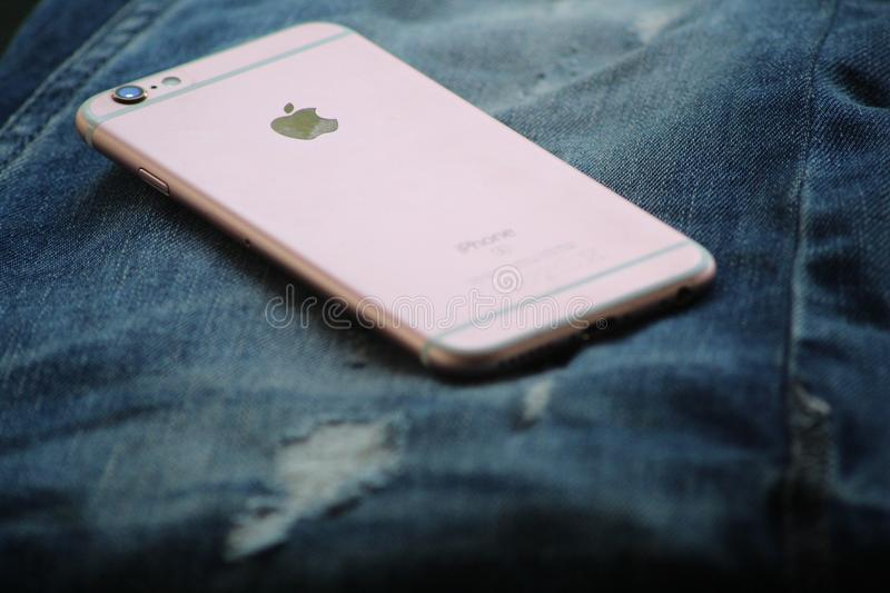 Close-Up Photography of Rose Gold Iphone 6s on Top of Blue Denim Jeans royalty free stock images