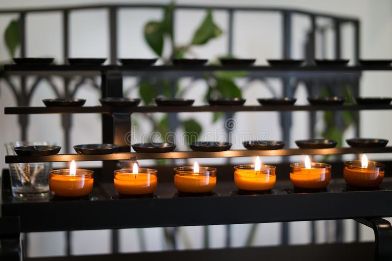 Close Up Photography of Tealight Candles on Black Metal Rack stock image