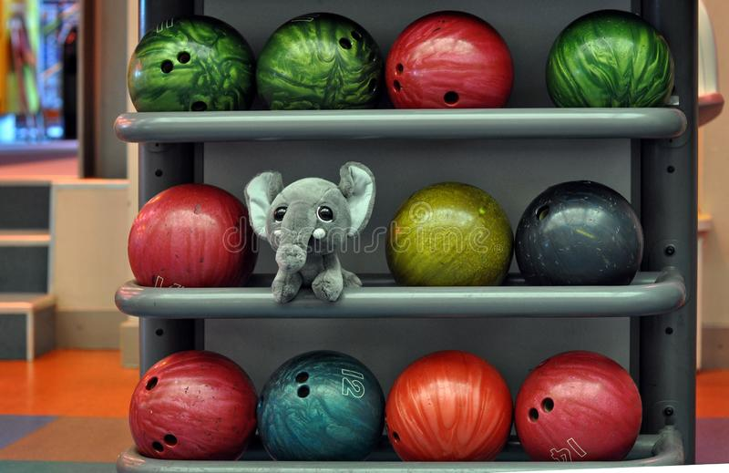 Close-up photography. Toy elephant between bowling balls.  stock photo