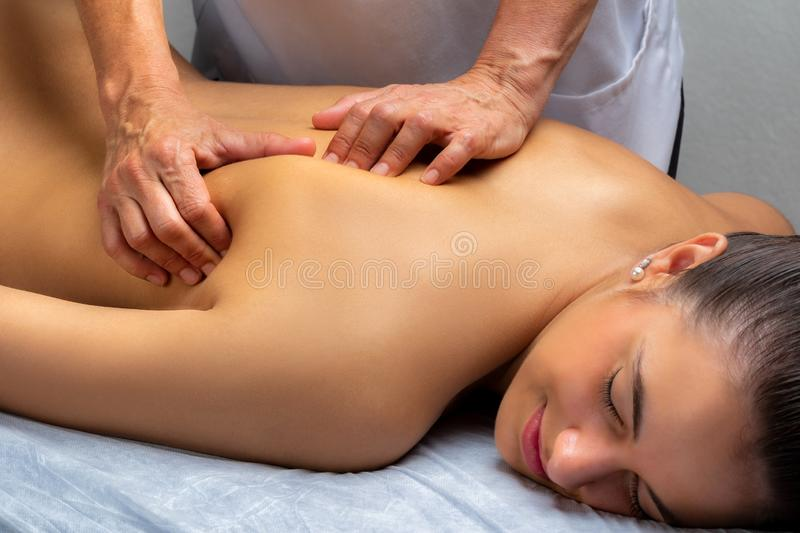 Physiotherapist manipulating shoulder blade on young woman. Close up of physiotherapist manipulating shoulder blade on young woman. Girl laying on spa bed with stock images