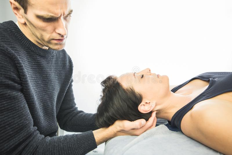 Close-up of a physiotherapist massaging the neck of a beautiful young woman. Concept of health treatments and physiotherapy royalty free stock photography