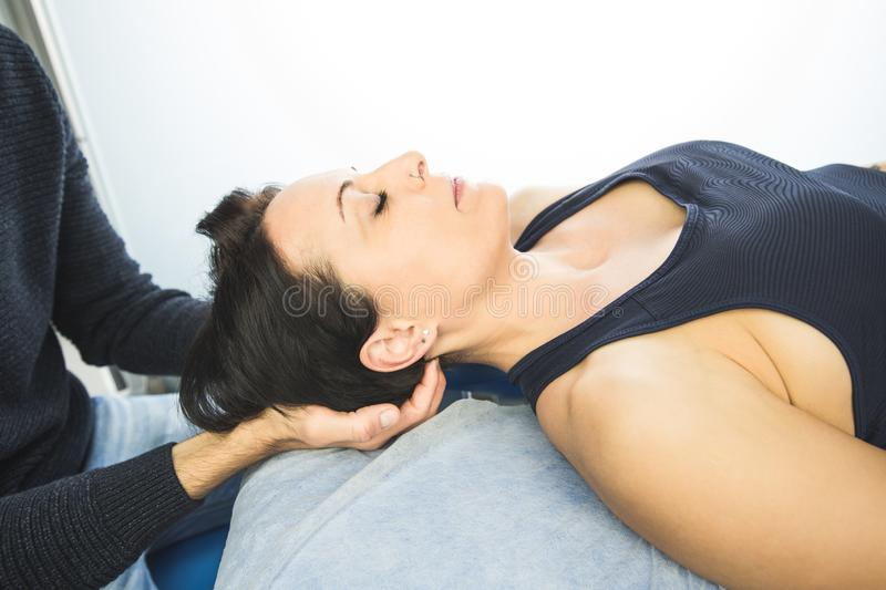 Close-up of a physiotherapist massaging the neck of a beautiful young woman. Concept of health treatments and physiotherapy royalty free stock photos