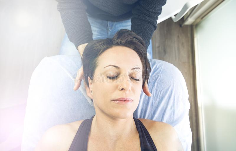 Close-up of a physiotherapist massaging the neck of a beautiful young woman. Concept of health treatments and physiotherapy royalty free stock images
