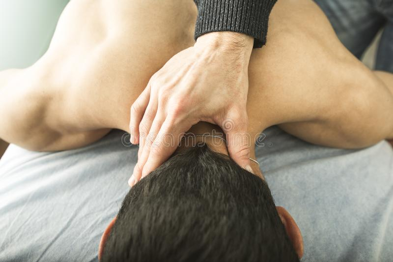 Close-up of a physiotherapist massaging the neck of a young man. Concept of physiotherapy and relaxation stock images