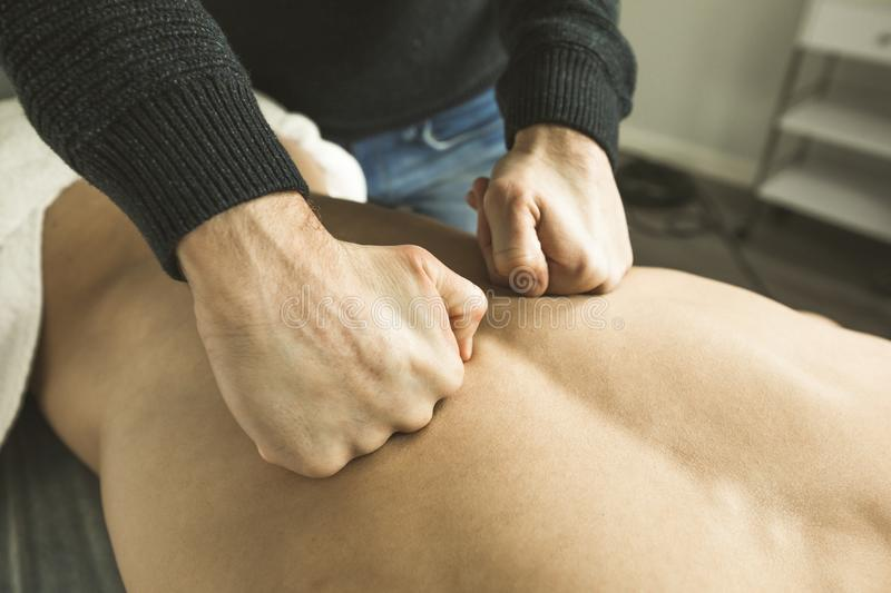 Close-up of a physiotherapist massaging a patient back. Physiotherapy treatment royalty free stock photography