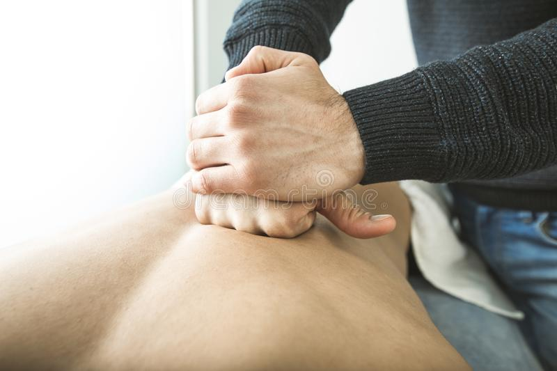 Close-up of a physiotherapist massaging a patient back. Physiotherapy treatment stock photography