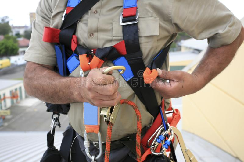 Close up pic of male industrial rope access worker wearing fall arrest, fall restraint safety protection harness royalty free stock photos