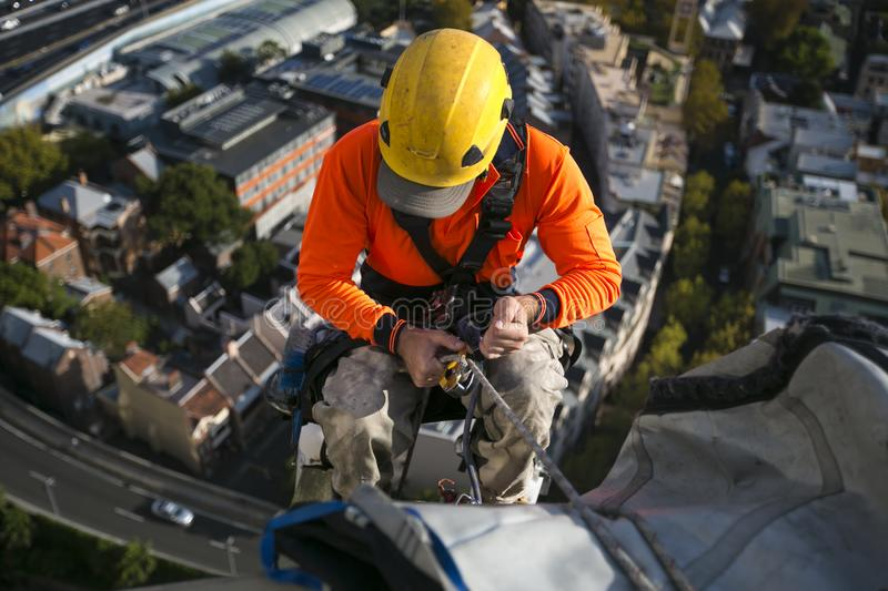 Close up pic of male rope access jobs worker wearing yellow hard hat, long sleeve shirt, safety harness, working at height stock photo