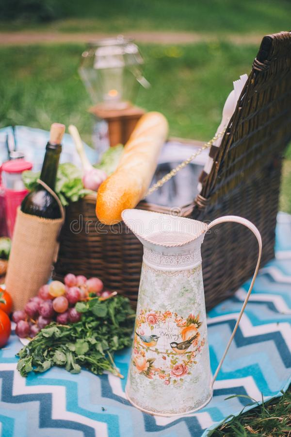 Close-up picnic in nature. Jug and food - greens, tomatoes, grapes, wine, baguette stock images