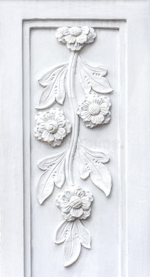 White flowers bas relief make from plaster. Close up picture background of white flowers bas relief make from plaster on the wall stock photos