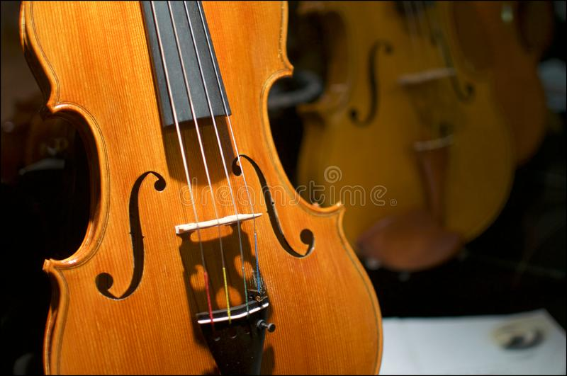 Close up picture of a beautiful wooden violin. Close up view of some beautiful illuminated Violins located inside a shop window in the city of Lugano, Ticino royalty free stock photo