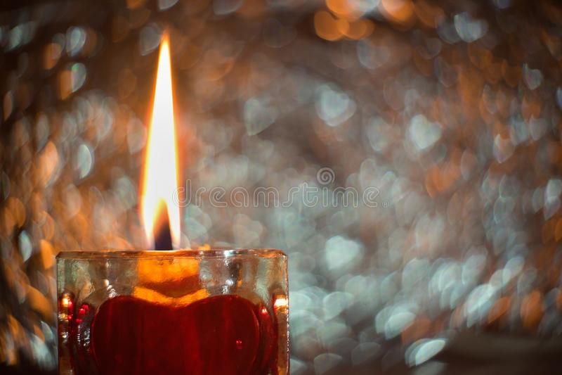 Close up Picture on the burning candle made from beeswax in the glass candle holder with red heart. Beside the flame is wild swirly bookeh background whith stock images