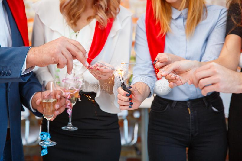 Close-up friends holding pretty Christmas sparklers on a blurred background. Sparkling bengal lights. stock photography