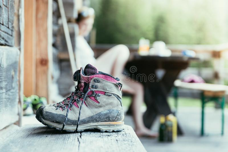 Trekking boots on the veranda of an alpine hut. Summer holidays in the mountains. Close up picture of hiking boots on a rustic wooden veranda of an alpine hut royalty free stock photos