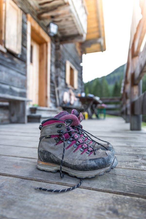 Trekking boots on the veranda of an alpine hut. Summer holidays in the mountains. Close up picture of hiking boots on a rustic wooden veranda of an alpine hut stock photo