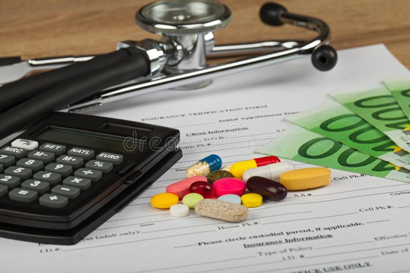 Expensive healthcare. Close up picture of medical insurance document, pills, calculator and money - Healthcare costs stock images