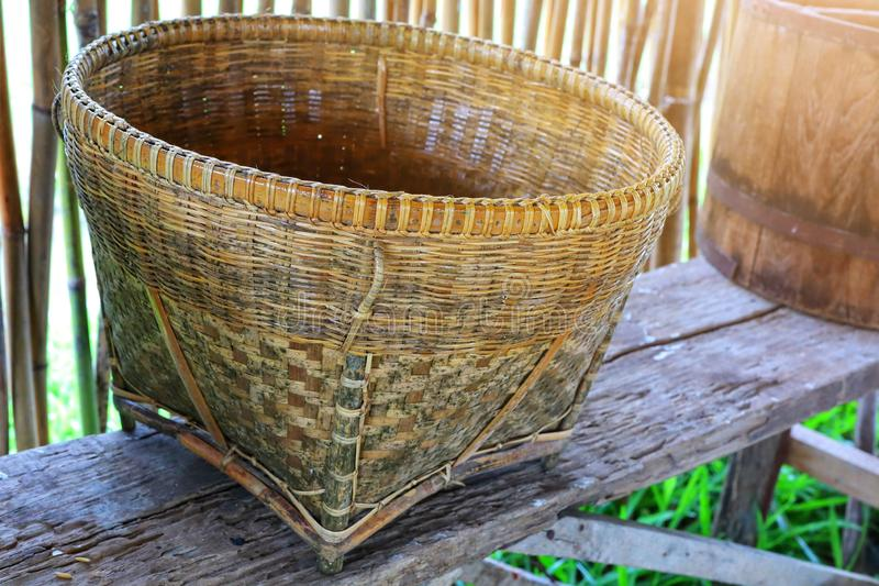 Close-up picture of old brown vintage Asian wooden basket placed on a wooden table, bamboo wall background. stock photos