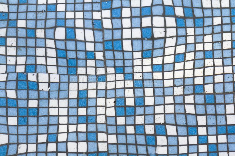 Close up picture of small square blue and white shiny ceramic tiles. Background, bathrooms and pools walls and floor design. royalty free stock photography