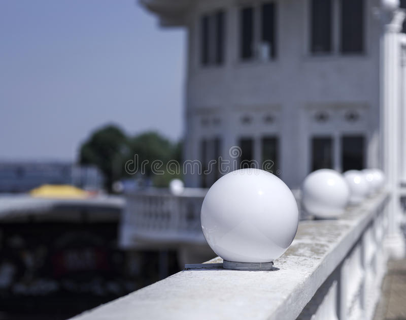 White round lanterns on a blurred natural background. A close-up of a spherical white glass plafond street lights. royalty free stock photo