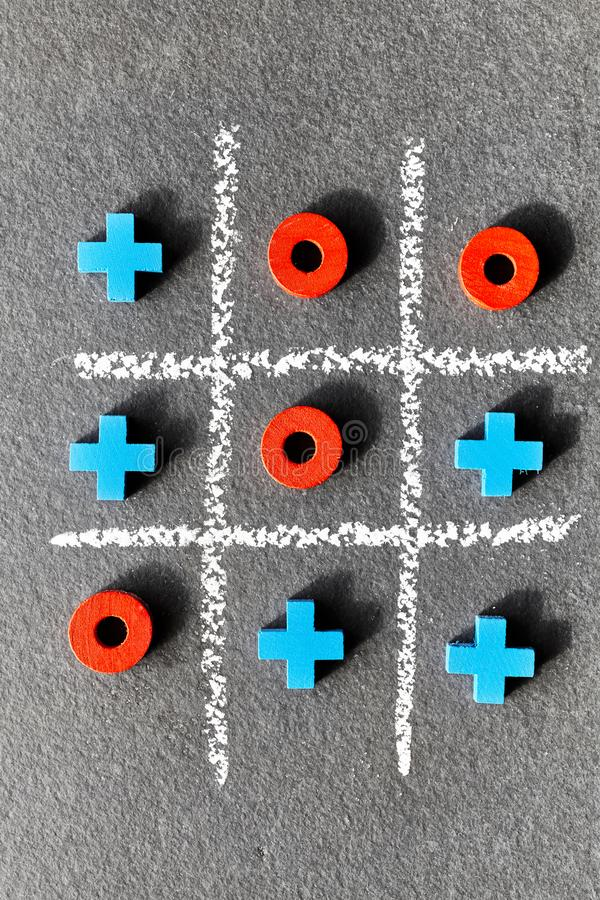 Tic tac toe game noughts and crosses on dark background. royalty free stock images