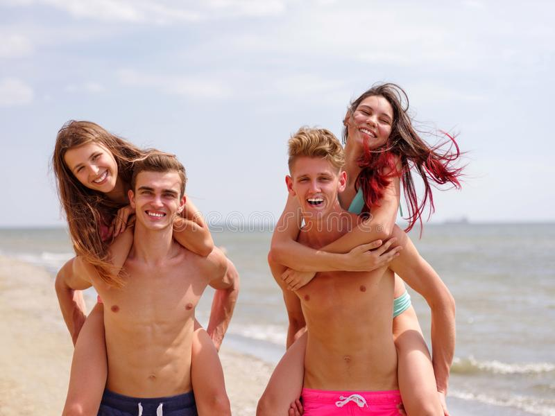 Boys, carrying a their girls on back, at the beach, outdoors. Close-up image of cheerful happy couples. Close-up picture of travel vacation and lifestyle stock image