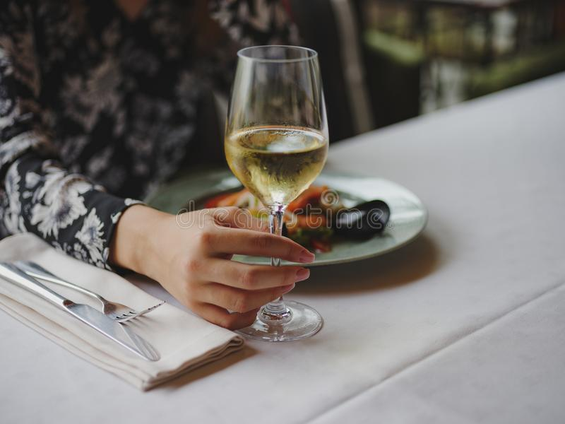Close-up of a woman at the restaurant. Lady holding wine on a blurred background. Luxurious lunch concept. Copy space. royalty free stock photography
