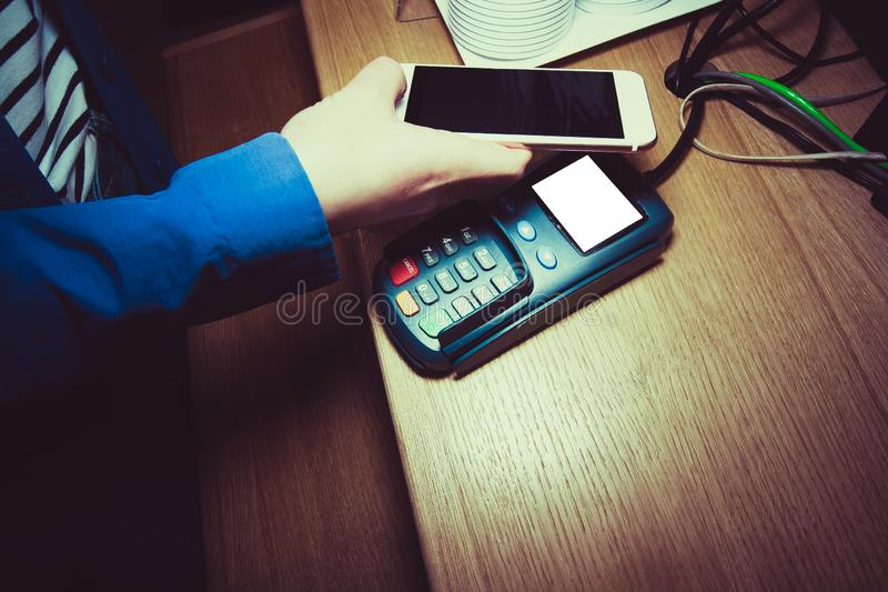 Close-up picture of a woman paying using PayPass on the phone in the shop. mobile payment ,online shopping concept stock image