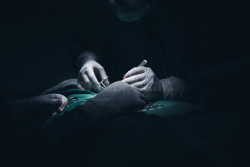 Close up picture of a young patient`s hand while the doctors inject the anestetic agent before surgical intervention in a dark, cr stock image